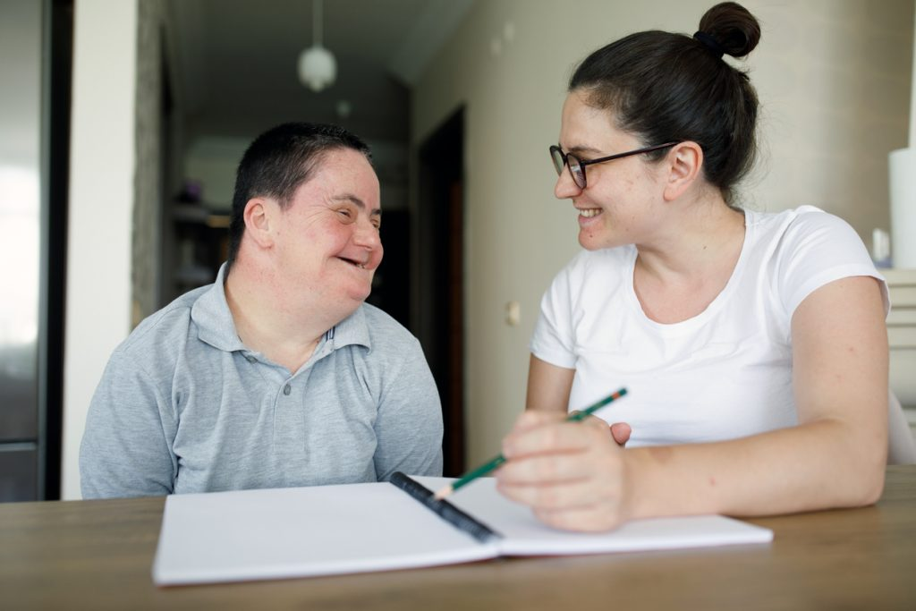 Young man with a disability working with an adult to list his preferences